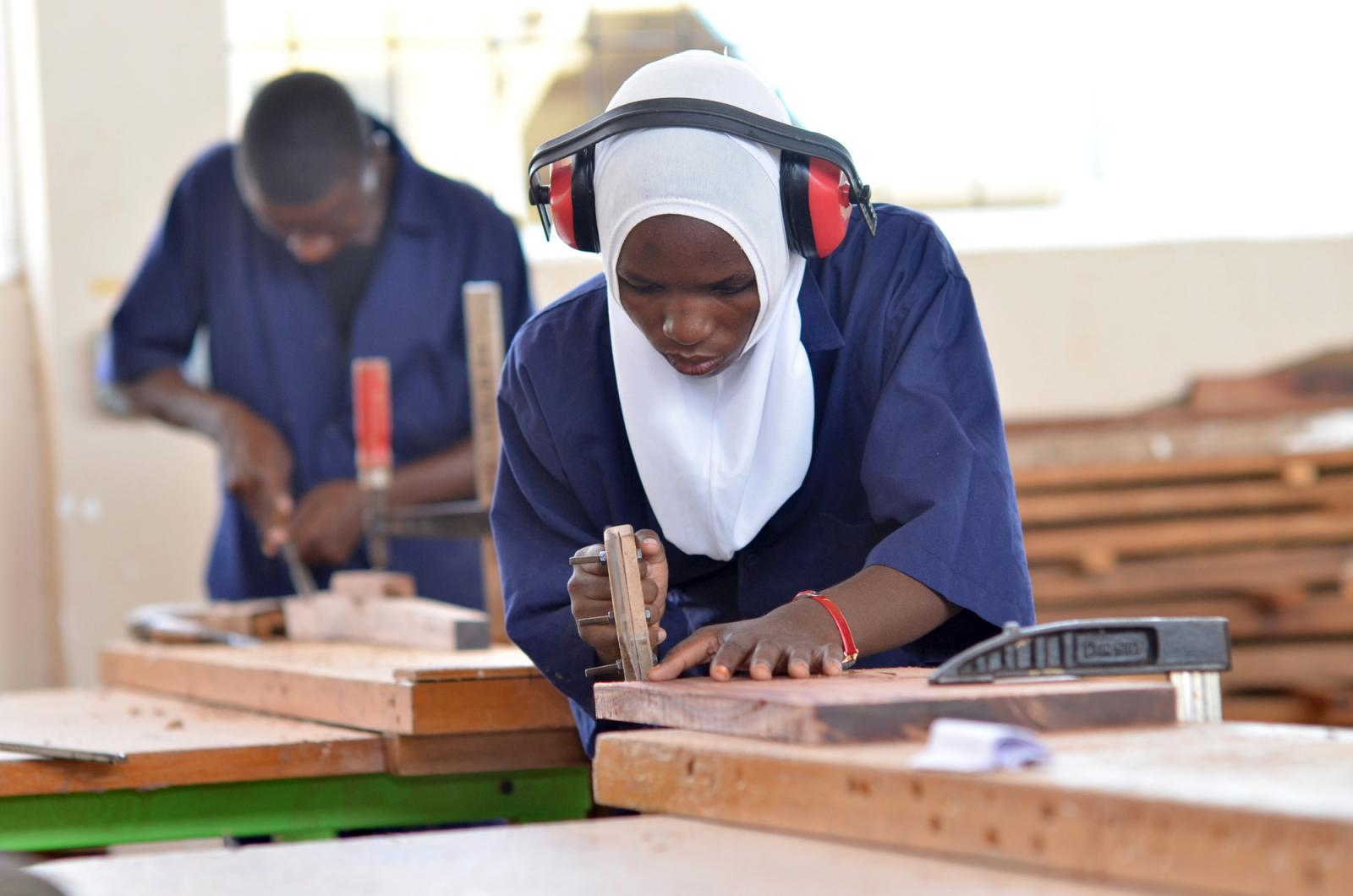 Second Year Vocational Training students, Mariam Hamis (L) works in Capentry Workshop at the Vocational Education Training Center (VETA) in Lindi, Tanzania.