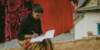 A woman sits on a low outdoor wall whilst writing in a log book