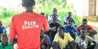 Peer educator Alfred Kunda stands in front of a group of seated young men, delivering an outdoor peer education session