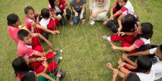 A group of young people sit in a circle on the grass, holding a web of string between them