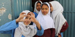 Young schoolgirls pose outside their classroom in Rawalpindi City