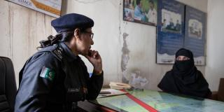 A female police officer sits across a desk from a civilian woman, in the police station