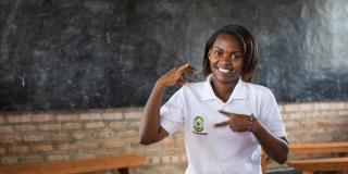 Volunteer Brown Niyonsaba smiles as she sits in front of a blackboard in the classrrom at Umutara School, signing 'VSO volunteer'