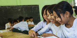 Three schoolgirls smile whilst sharing a textbook in the classroom at Kyakathone primary school, Mon state.
