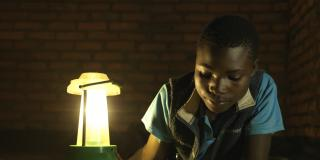 A child writing using a solar-powered lantern