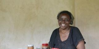 Celina Chibanda smiles as she holds a large jar of the peanut butter she produces