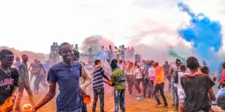 Young people in Loitokitok, Kenya throw pots of brightly-coloured powdered paint as part of the ICS-organised 'Colourfest'
