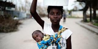 Sister carries brother in Mozambique