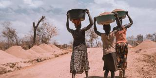 Women carry basins down a track in Rhino Camp, Uganda.