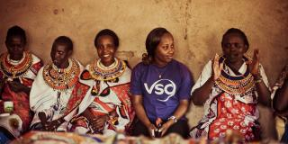 A volunteer in a VSO T-shirt sits in a row with other women, who are wearing traditional dress
