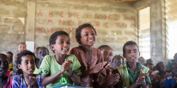 Ethiopian children sat in a class, smiling and clapping their hands