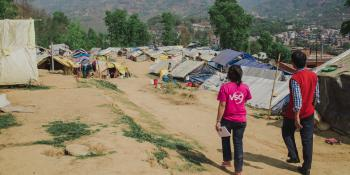 Two people, one in a VSO t-shirt, survey a camp for internally displaced people