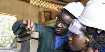 A student watches intently as her instructor demonstrates machinery in a welding and metal workshop