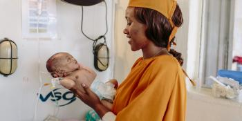 A female nurse smiles at a newborn baby she's holding in the neonatal intensive care unit