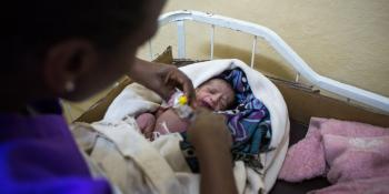 A midwife tends to a newborn baby who is wrapped in colourful blankets
