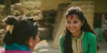 Nirmala smiles as she sits on the floor to talk with 'Big Sister' Durga