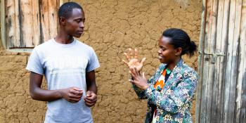 A young man and young woman stand outside, conversing in Rwandan Sign Language