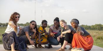 A team of female ICS volunteers crouch down and pose together