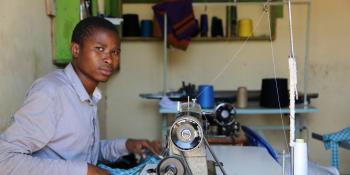 A young male tailor works at a sewing machine
