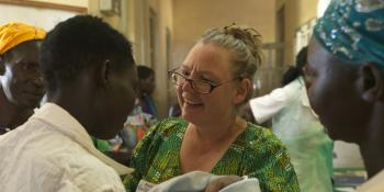 Joanne Awol is congratulated by midwife Gudrun after giving birth to a baby girl.