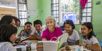 VSO Volunteer Ana Paula Pinto reads textbook and performs in classroom activity with the students from primary school at Kyakathone primary school, Myanmar