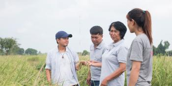 Volunteering in Cambodia. Farmer Ly Theort talks with international volunteers in one of her fields