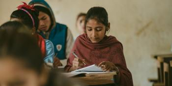 Little Sister Pramila writes in her exercise book in a classroom