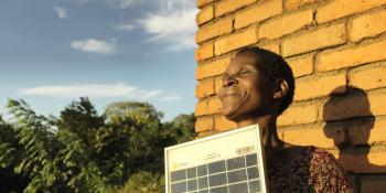 Solar Mama Dines smiles as she stands outside in the sun holding a solar panel
