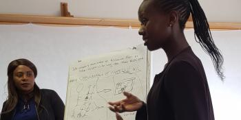 A young woman stands and presents a flipchart showing a diagramme outlining young people's frustrations with healthcare