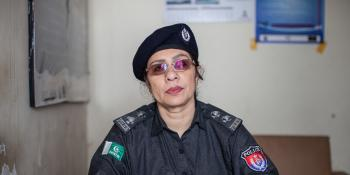 A female police officer sits behind her desk in the police station