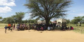 A large group of parents gather under a tree as children begin a dance performance at Archerer primary school