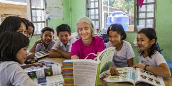 Volunteer Ana Paula Pinto sits and reads with children in Kyakathone primary school