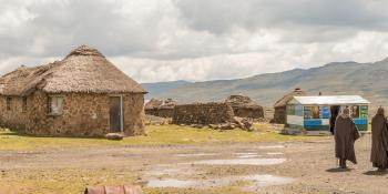 Landscape view of Lesotho, featuring traditional stone buildings in the foreground and mountains in the distance