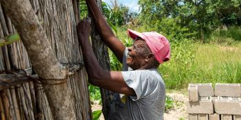 A man works to rebuild a house damaged by Cyclone Idai in 2019