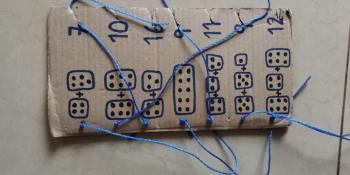 A piece of cardboard with diagrammes and numbers to help pupils learn simple addition