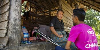 VSO national volunteer Kaung Khant speaks to a villager on the front porch of his house as part of his work identifying vulnerable residents to prepare for disaster.