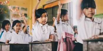 cambodia school girls stood at desks with their hands in the air
