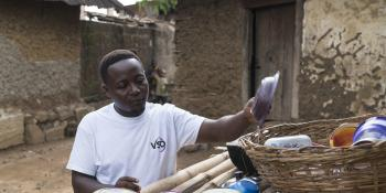 Community volunteer James Lansana puts dishes out to try on an outdoor bamboo rack