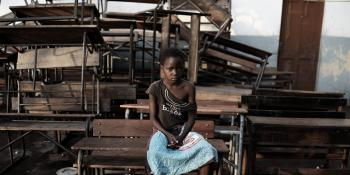 Celia, 12, sits in front of some damaged school tables after Cyclone Idai