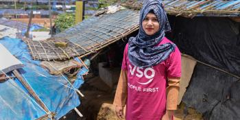 A volunteer in a VSO T-shirt stands in front of a temporary learning centre in the Cox's Bazar refugee camp