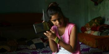 Girl in Nepal listening to radio lessons during COVID-19 lockdown
