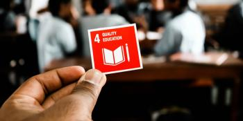 "Close up of a hand holding a small red card with ""4 - Quality Education"" written on it"