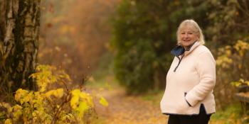 Volunteer Carol Carson walks in woodland in Scotland