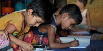 Two young Rohingya boys sit on the floor of a child-friendly centre in the Cox's Bazar camp, drawing with colouring pencils