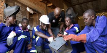 A group of students in blue overalls and safety gear crouch down around a metal box as they are taught by a lead instructor