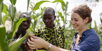 Randstad volunteer Jenny Hoevenagel looks at crops in a field next to members of a youth co-operative