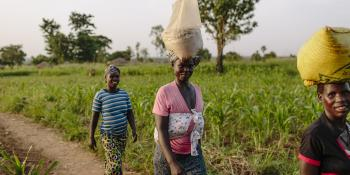 Ugandan female farmer carries grain on her head as part of VSO's YELG project