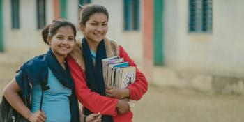 16-year-old Nirmala smiles with her friend, who is carrying a pile of schoolbooks.