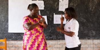 Brown Niyonsaba teaching sign language to community health worker Judith Mugirente