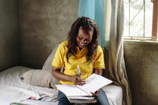 A young Mozambicuan woman sits on her bed to study